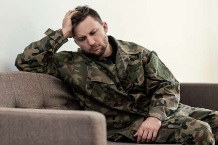 Unhappy and sad soldier in green moro uniform with war syndrome