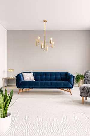 Minimal living room interior with a blue sofa and lots of empty space on the floor and on the background wall. Real photo. Stock Photo