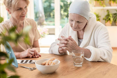 Psychologist and patient sitting together at a table in a nursing home Stock Photo