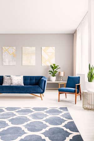 Eenvoudig woonkamerinterieur met een groot vloeroppervlak met een tapijt. Bank en fauteuil op de achtergrond. Echte foto. Stockfoto