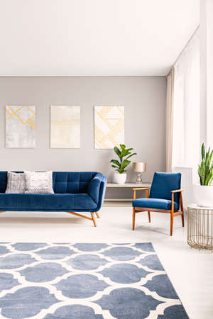Simple living room interior with a big floor space with a rug. Couch and armchair in the background. Real photo.