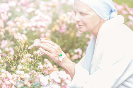 Senior with cancer enjoying flowers in a garden