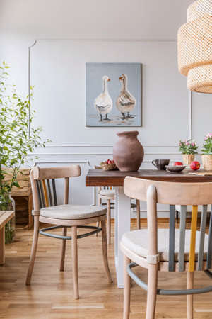 Holzstühle am Tisch im natürlichen weißen Esszimmerinnenraum mit Plakat und Lampe. Echtes Foto