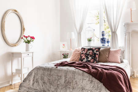 Sweet bedroom interior with a bed covered with a silver throw, a burgundy brown blanket and many cushions. Real photo.