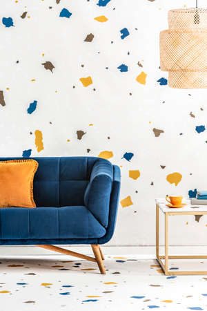 Plywood lampshade above a side table with golden frame and a dark blue sofa in a white living room with lastrico pattern. Real photo. Stockfoto - 108248994