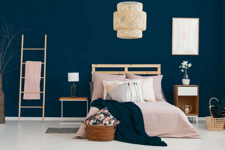 Wicker lamp hanging above double bed in real photo of bedroom interior with dark blue wall, flowers on bedside table and ladder with blanket Foto de archivo - 108249014