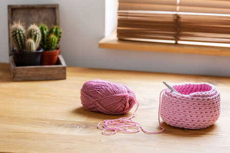 Pink yarn and craft on wooden desk with cactus in home office interior. Real photo Stok Fotoğraf