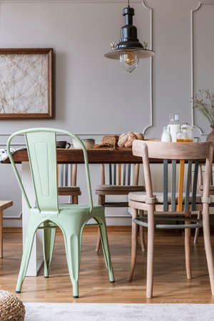 Chairs at wooden table under lamp in bright dining room interior with poster on the wall. Real photo