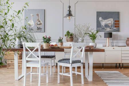 Witte stoelen aan tafel met bloemen in rustieke eetkamer interieur met lamp en posters. Echte foto Stockfoto
