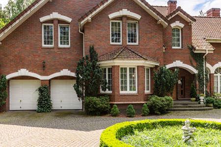 Echtes Foto eines Backsteinhauses mit Erkerfenster, Garagen und rundem Garten vor dem Eingang Standard-Bild