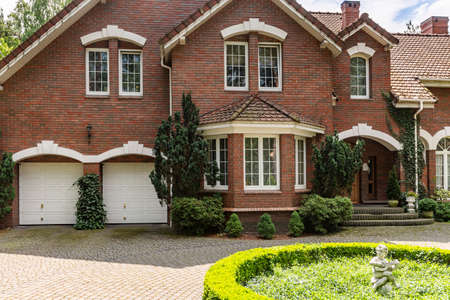 Real photo of a brick house with a bay window, garages and round garden in front of the entrance