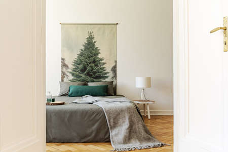 A peek through an open door into a simple style bedroom interior with a bed dressed in gray and green sheets, pillows and a wool blanket. An evergreen tree poster on a background wall. Real photo. Stock Photo
