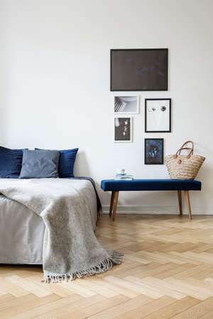 Grey blanket on bed with blue pillows in white bedroom interior with posters above bench. Real photo