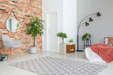 Mirror on red brick wall above grey armchair in apartment interior with plants and bed. Real photo Фото со стока