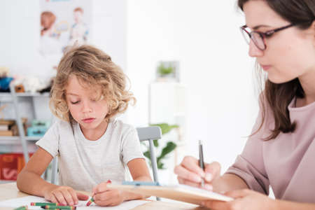 Child drawing pictures during meeting with therapist for orphans