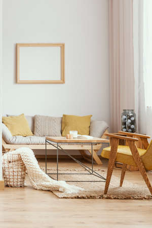 Yellow wooden armchair and sofa in white living room interior with mockup of empty poster. Real photo