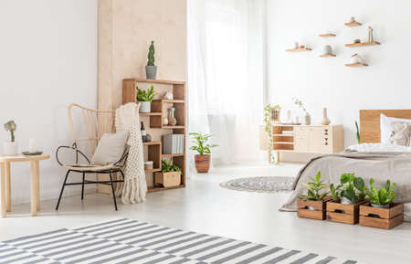Armchair next to wooden table and carpet in bedroom interior with plants in front of bed. Real photo