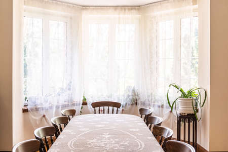 Old style dining room interior with a big window decorated with curtains, table with chairs and plant. Real photo