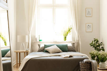 Natural bedroom interior with a bed surrounded by bunches of wild flowers. Big sunny window in the background. Real photo. Banco de Imagens