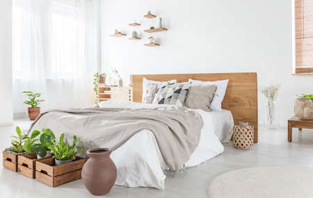 Pillows and sheets on wooden bed in bright bedroom interior with plants and windows. Real photo Archivio Fotografico - 108320401