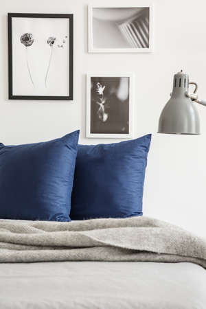 Grey blanket and navy blue cushions on bed in bedroom interior with posters and lamp. Real photo