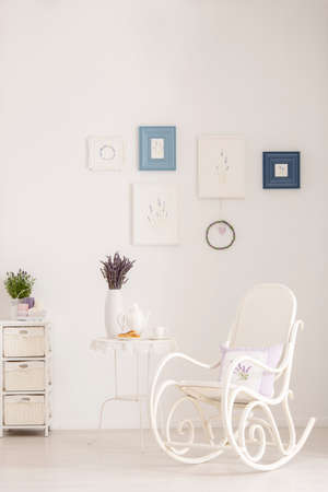 Rocking chair next to table with lavender flowers in white living room interior with posters. Real photo Stock fotó