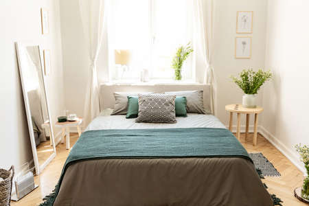 A big bed dressed in earth colors linen with cushions and a blanket standing in an eco friendly bedroom interior. Real photo.