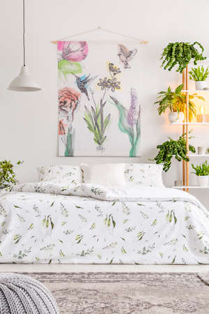 Natural bright bedroom interior with a comfortable bed dressed in organic cotton white linen with green print. Flowers and birds painted on the fabric above the bed. Real photo.