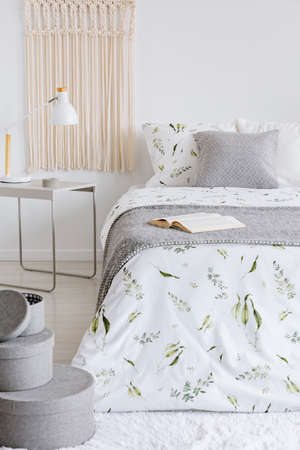A cozy pastel bedroom interior with a bed dressed in green plants on white linen and cushions. Warm gray wool blanket on the bed. Real photo.