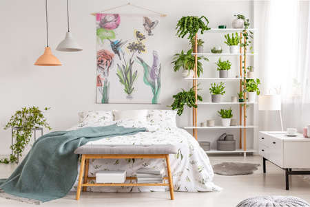Close to nature bright bedroom interior with a bed covered with white sheets and marine blanket. Green plants on shelves next to the bed. Real photo.