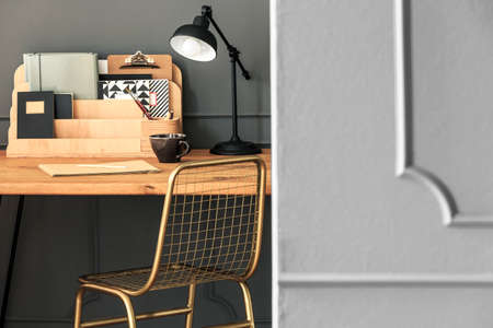 Gold chair at wooden desk with lamp and organiser in grey workspace interior. Real photo 版權商用圖片