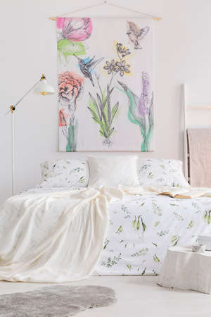 Vertical view of a scandinavian style bedroom interior with a bed dressed in white linen with painted green plants. Fabric wall art with colorful birds and flowers above the bed. Real photo. 스톡 콘텐츠