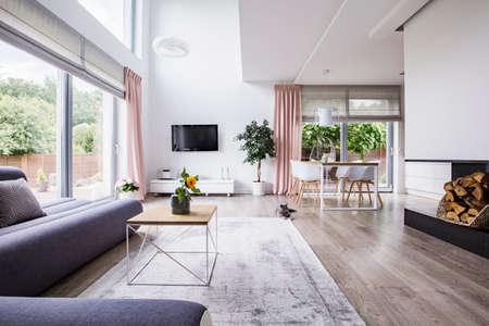 Echtes Foto eines Essbereichs, des Fernsehers und der grauen Couch im offenen Innenraum des Wohnzimmers