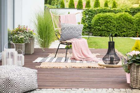Echte foto van een wit kussen en een roze deken op een rotanstoel die in de tuin van een luxueus huis staat Stockfoto