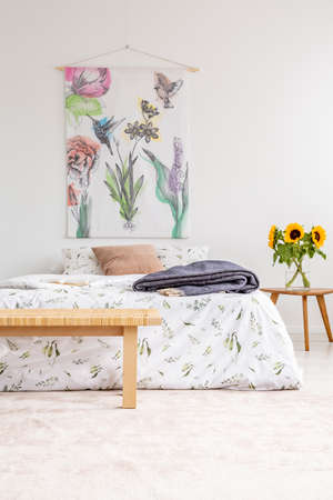 Cottage house minimal bedroom interior with colorful flowers and birds painted on fabric above a bed which is dressed in natural textile sheets. Sunflowers by the bed. Real photo.