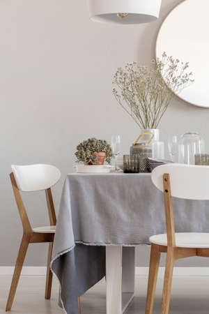 Witte stoelen en tafel in een elegante en pastel eetkamer interieur. Echte foto Stockfoto