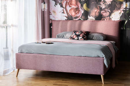 Grey sheets on pink bed in bright modern bedroom interior with flowers print on the wall. Real photo