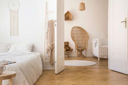 Weißes Apartment-Interieur mit Fischgrätenparkett, Doppelbett und offener Tür zum Kinderzimmer mit Pfauenstuhl, weißem Kinderbett und rundem Teppich auf dem Boden Standard-Bild