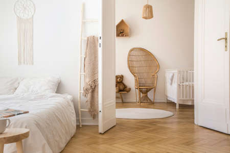 Wit appartementinterieur met visgraatparket, tweepersoonsbed en open deur naar kinderkamer met pauwenstoel, witte wieg en rond tapijt op de vloer Stockfoto