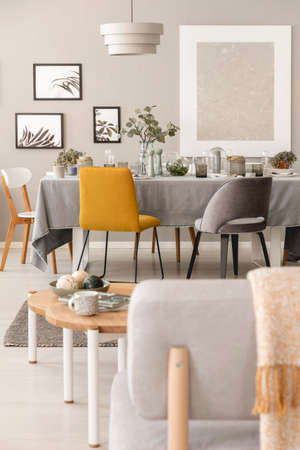 Real photo of a scandi dinner room interior with a yellow chair next to a table. Close-up of a chair