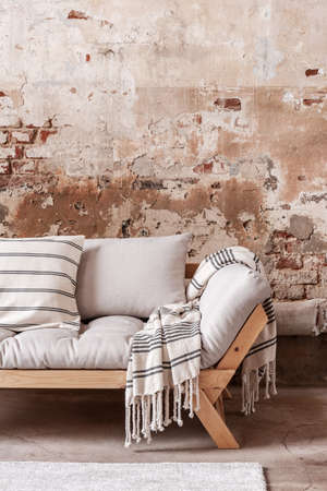 Patterned blanket and pillows on wooden grey couch against red brick wall in flat interior. Real photo