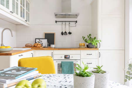 Close-up of a table with fruit, plants and magazines in a bright kitchen interior. Cupboards in the background. Real photo