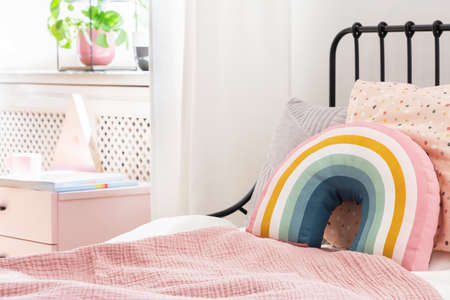 Pastel pillows on pink bed in girls rainbow bedroom interior with white cabinet. Real photo Stockfoto