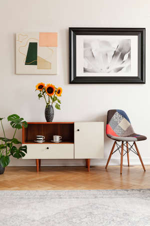 Framed photo and abstract art above sunflowers on an elegant cabinet and a patchwork chair in white living room interior. Фото со стока