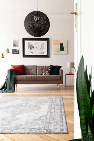 Low angle view of an artistic living room interior with a large, black, spherical pendant light above a brown sofa. Stock Photo
