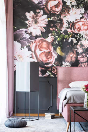 Books and grey pillow next to pink bed in patterned bedroom interior with flowers wallpaper. Real photo