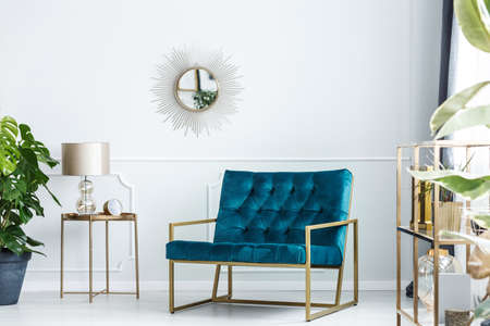 Sunburst mirror on a white wall of a fancy living room interior with golden furniture and a modern, turquoise blue sofa