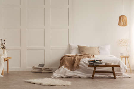 Fur and wooden stool in front of bed with blanket in white bedroom interior with lamp. Real photo