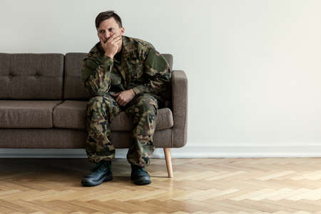 Depressed professional soldier in green uniform sitting alone at home. Copy space on the wall Stock Photo