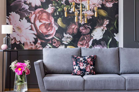 Real photo of a flower print behind a couch in a living room interior with fresh flowers in a vase Foto de archivo